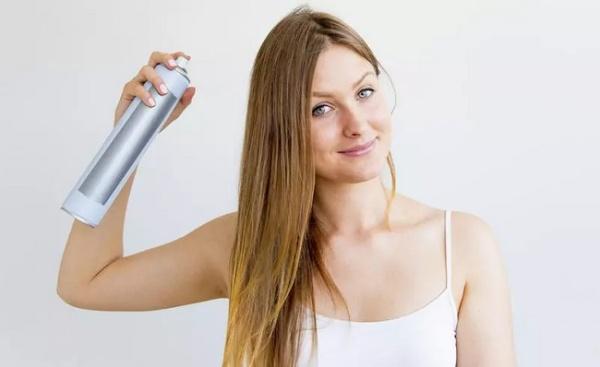 Woman Sprays Dry Shampoo Into Her Hair